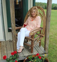 Author Debra Clopton sitting on the porch of her office